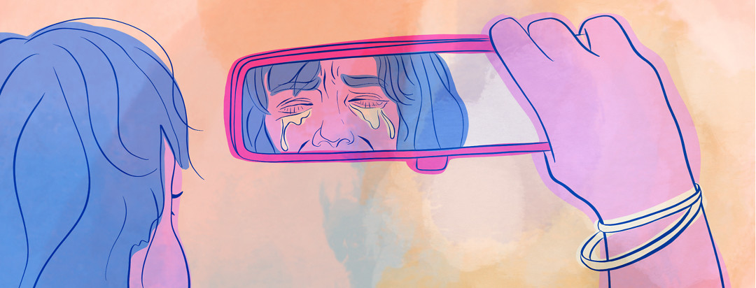 A woman with axial spondyloarthritis clutches the rearview mirror inside of her car and looks at her crying reflection.