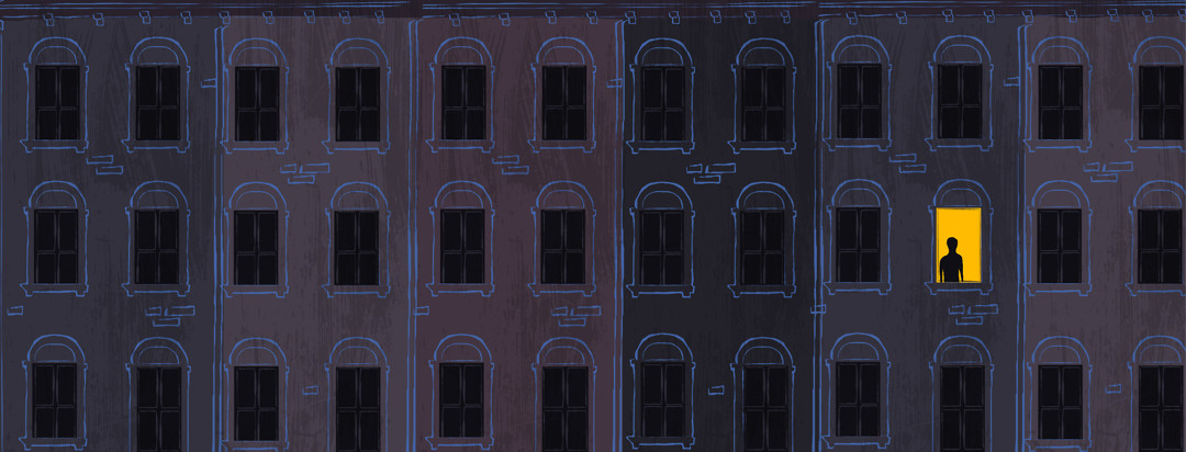 Silhouette of a person in the one lit window in a row of dark houses at night.