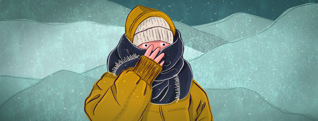 A person bundled up in winter weather clothing outside, clutches their scarf closely to their face.