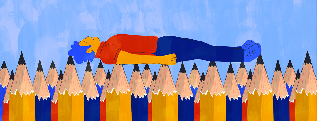 A man lays flat on a bed of sharp pencils.