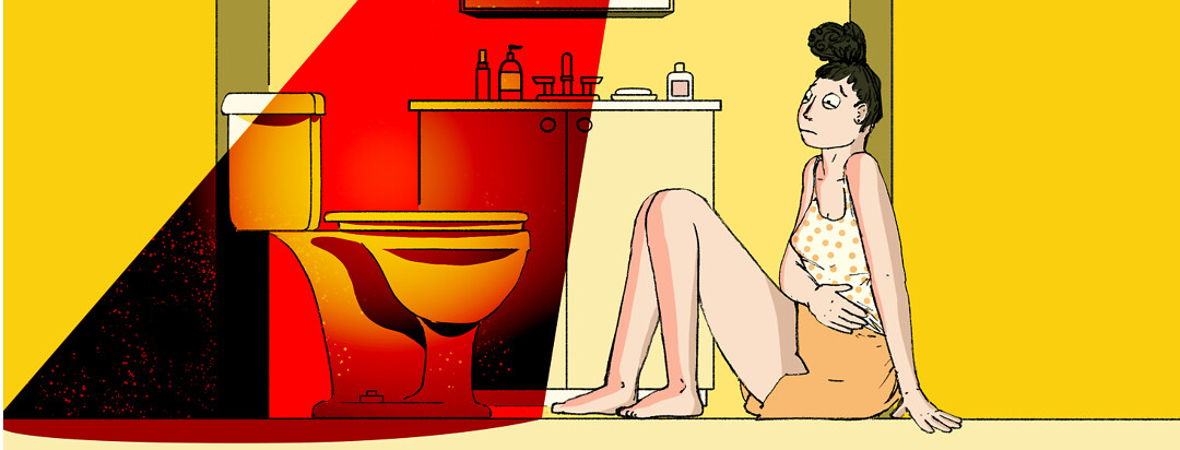 A woman sits on the bathroom floor, clutching her stomach in pain.