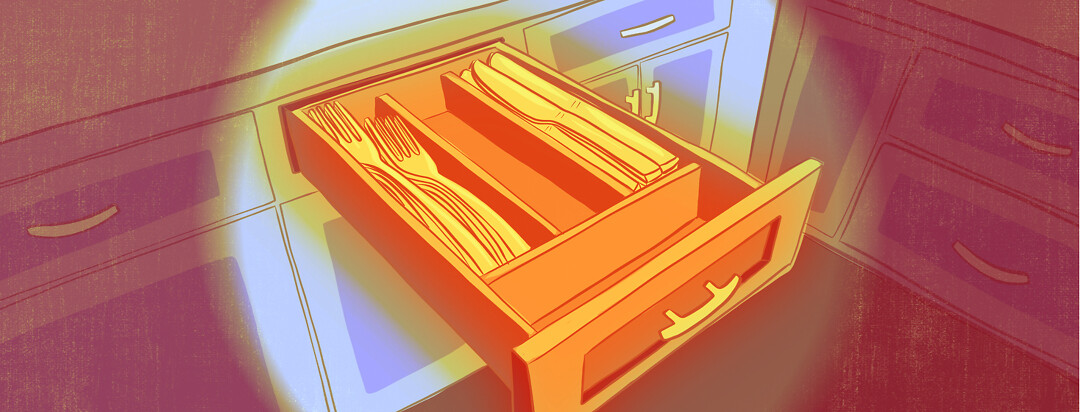 An open utensil drawer showing plentiful forks and knives, but an empty compartment where spoons should be.
