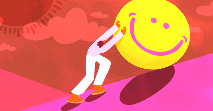A person pushing a giant sphere up a hill with a happy face on it.