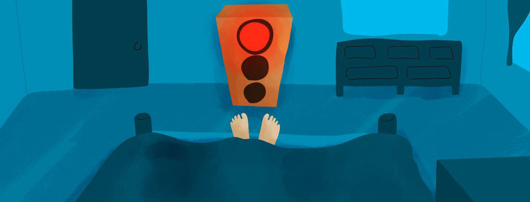 A stoplight on red at the foot of a bed, where feet peek out from under the covers.
