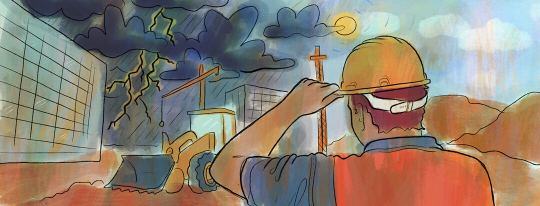 A worker with a hard hat on a construction site looks off into the distance showing an impending thunderstorm.